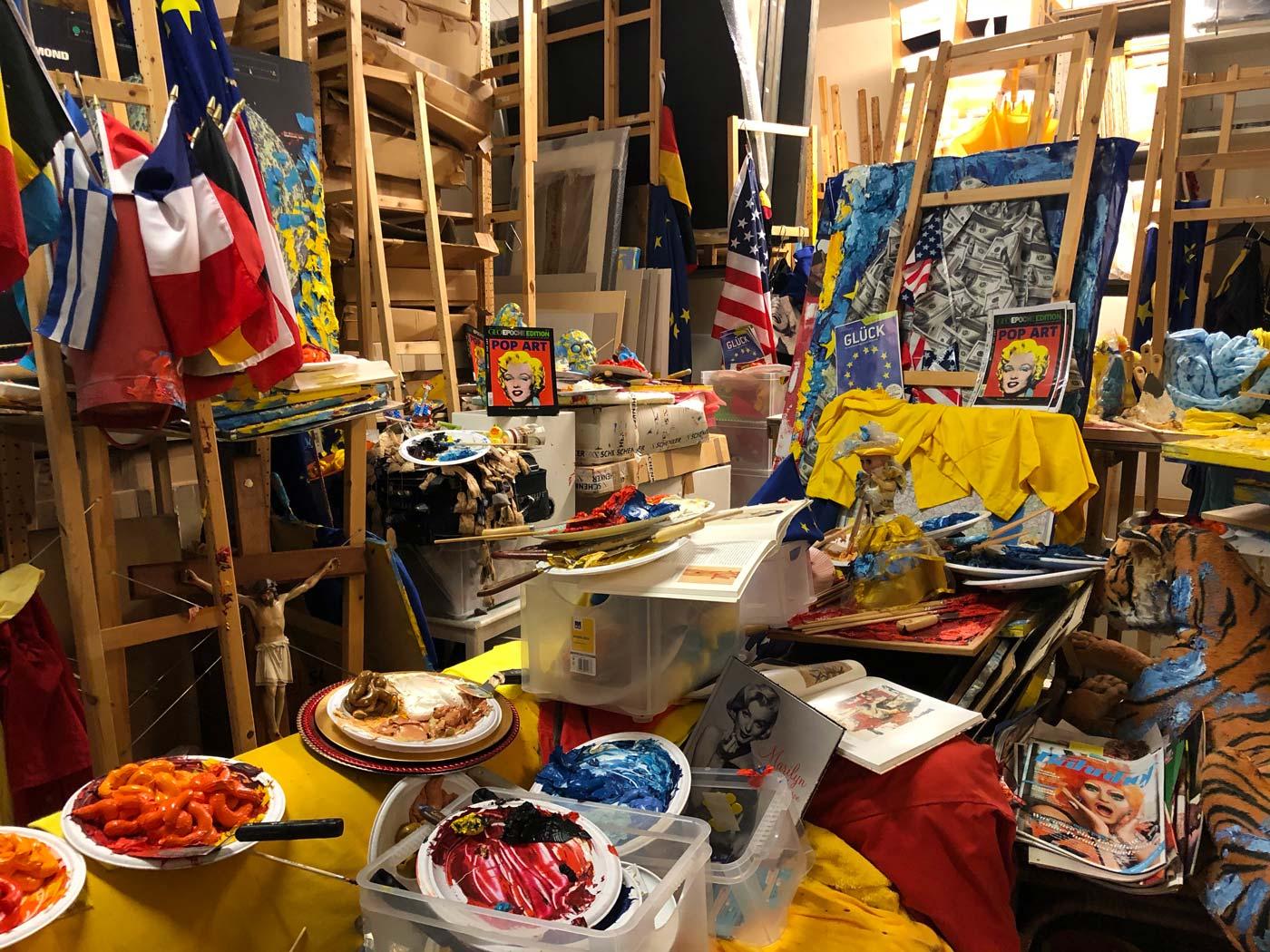 chaotisches Atelier mit Gemälden, offenen Farben, Staffeleien und Fahnen