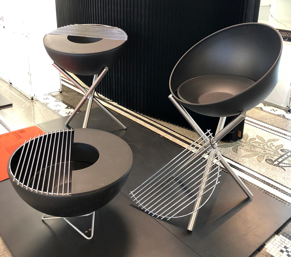 Präsentation dreier Holzkohlegrills in schwarz auf je drei Metallbeinen