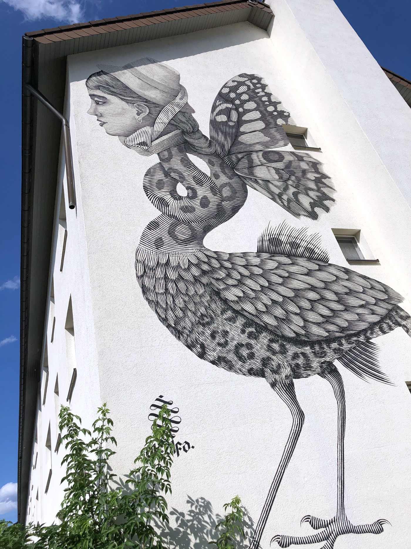 weißes Haus mit riesigem Gemälde eines Menschen mit Tierrock und Flügeln