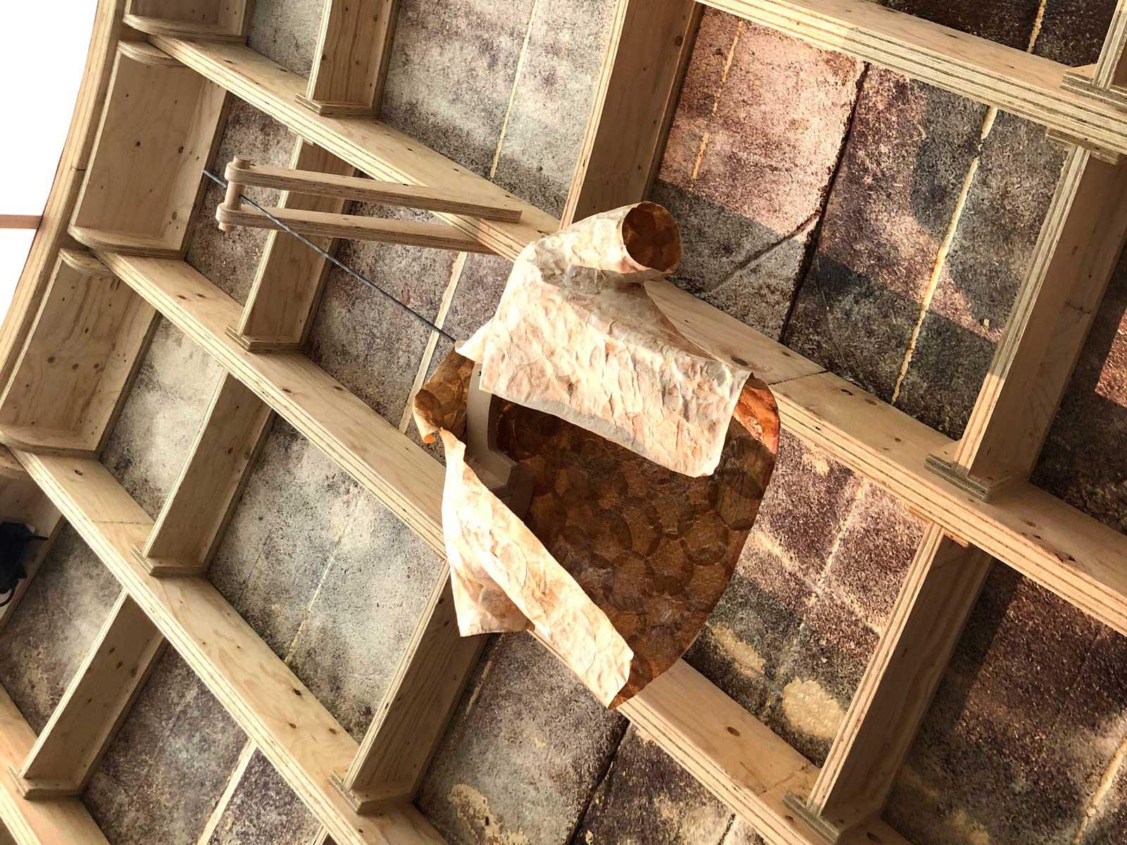 Raum mit Holzstreben und Holzplatten, in dem ein T-Shirt aus nachhaltigen Materialien hängt