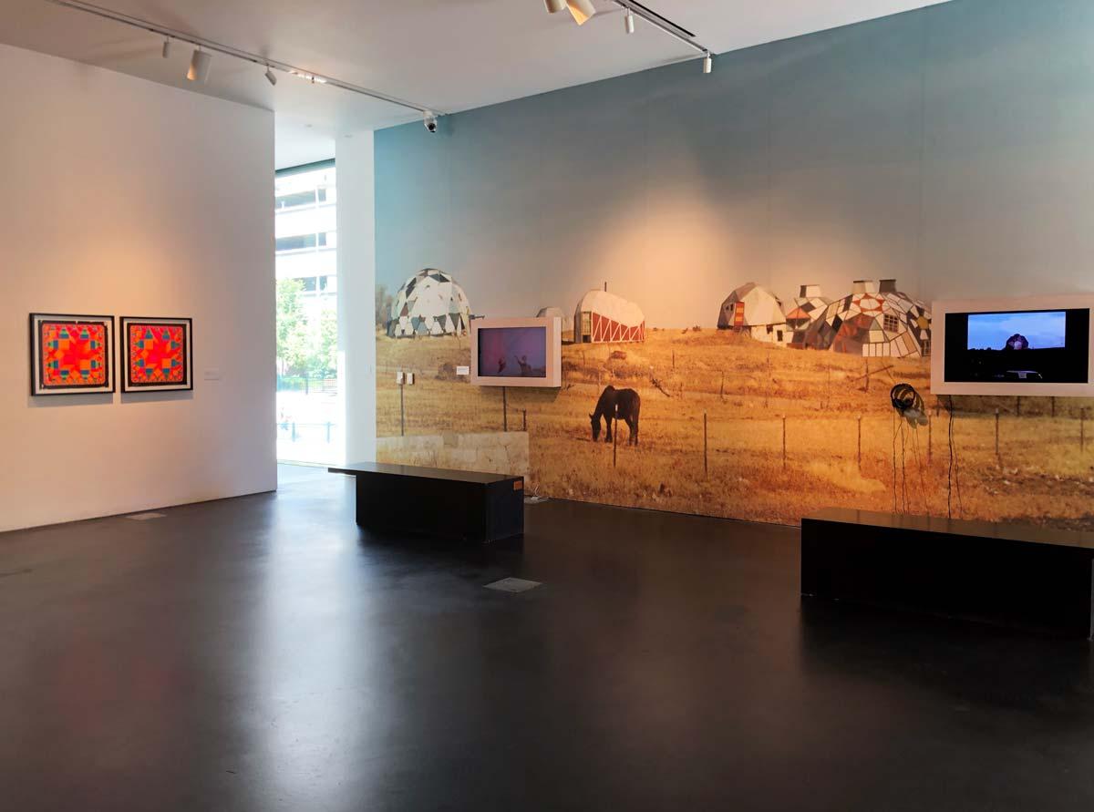Ausstellungsraum mit Screens und einem großen Wandbild mit kuppelförmigen Häuschen