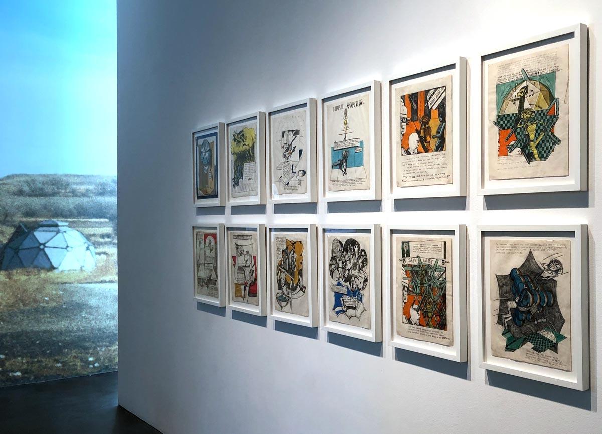Ausstellung mit eingerahmten, bunten Illustrationen an der Wand