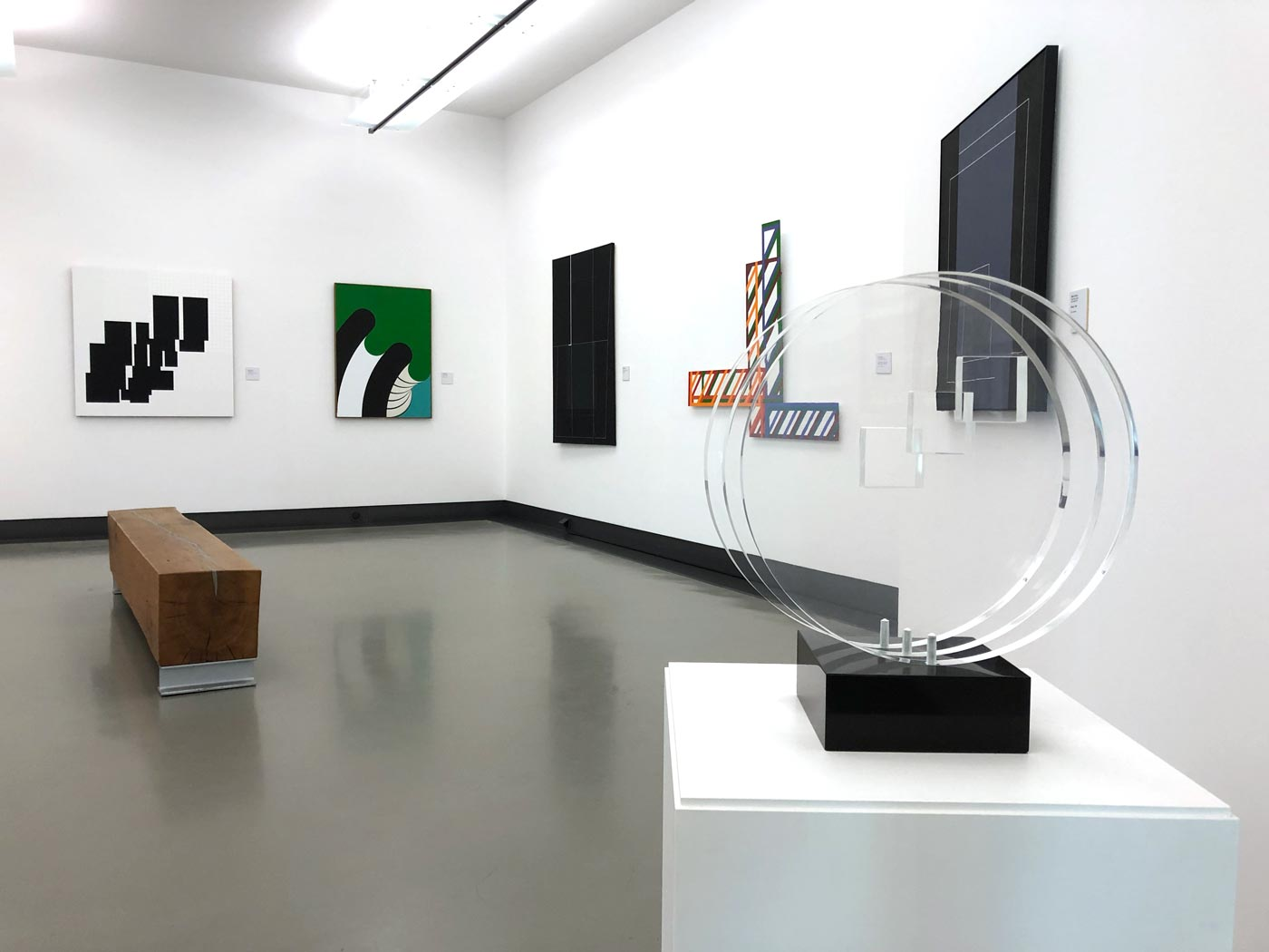 Ausstellungsraum mit skulpturalen Exponaten und Bildern an den Wänden