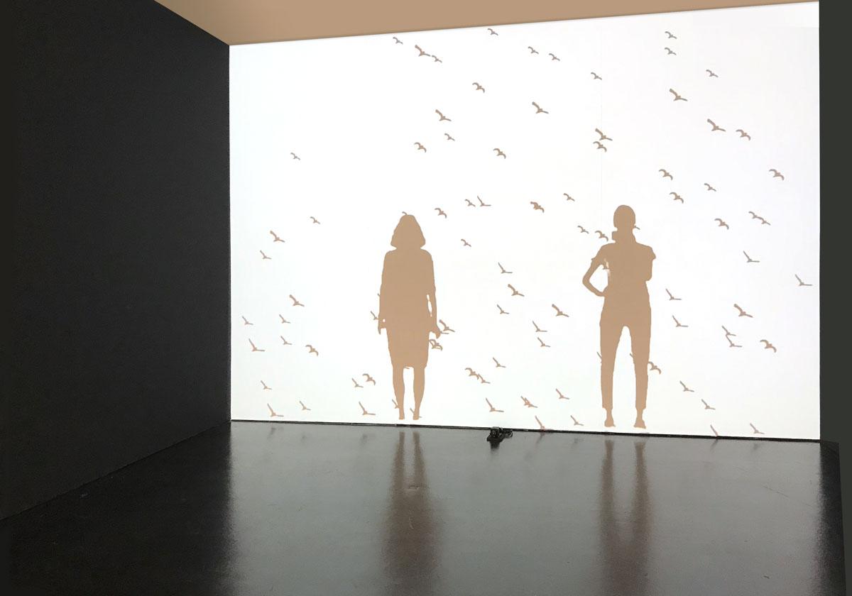 Leinwand mit dem Schatten zweier Personen und einem Vogelschwarm