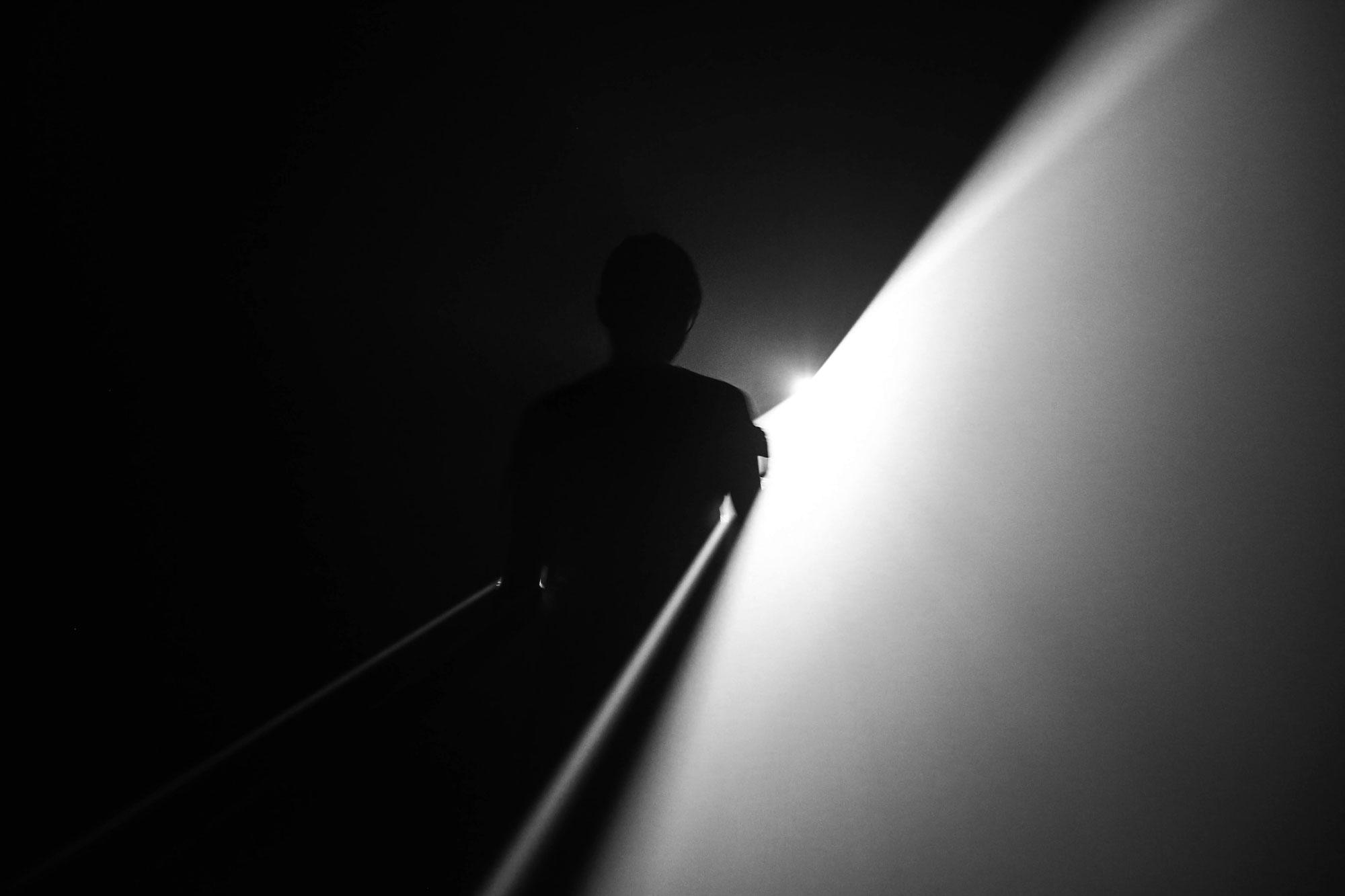 Ein schwarzer Raum, nur von einem Lichtkegel durchbrochen, der den Schatten einer Person sichtbar werden lässt