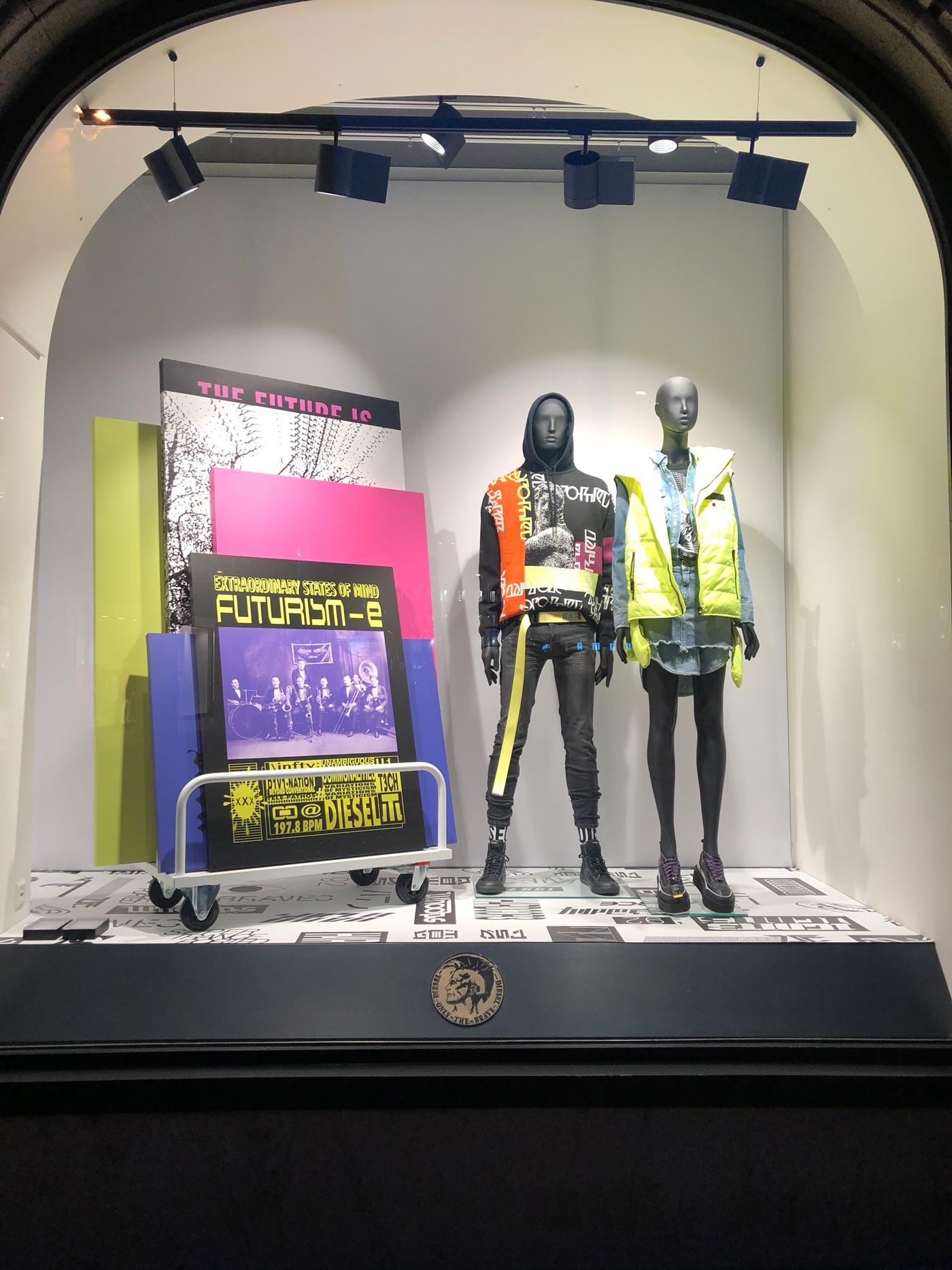 Schaufenster mit zwei beleuchteten, bunt bekleideten Puppen