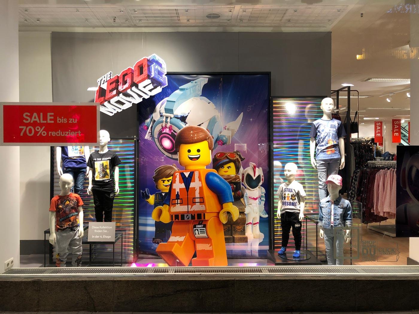 riesengroßes Legomännchen und Schaufensterpuppen mit Kinderbekleidung