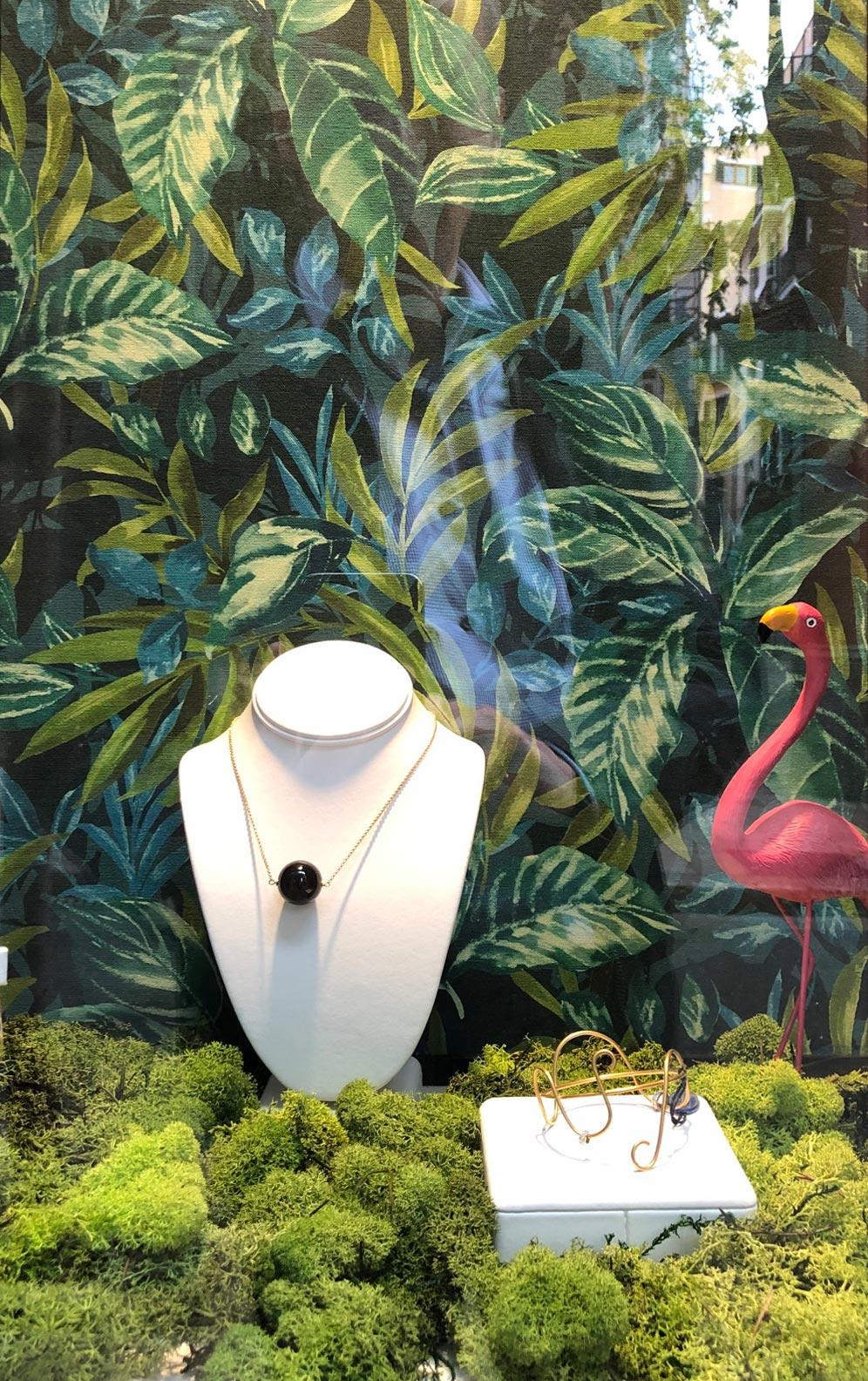 Schaufenster mit Schmuck und Urwalddekoration und einem Flamingo