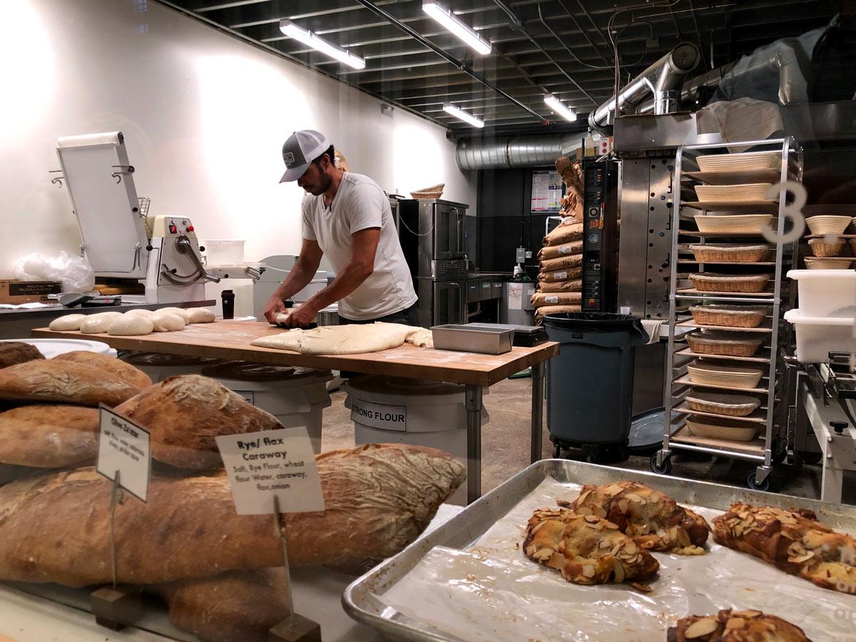 Junger hipper Bäcker in seine Arbeit viertieft