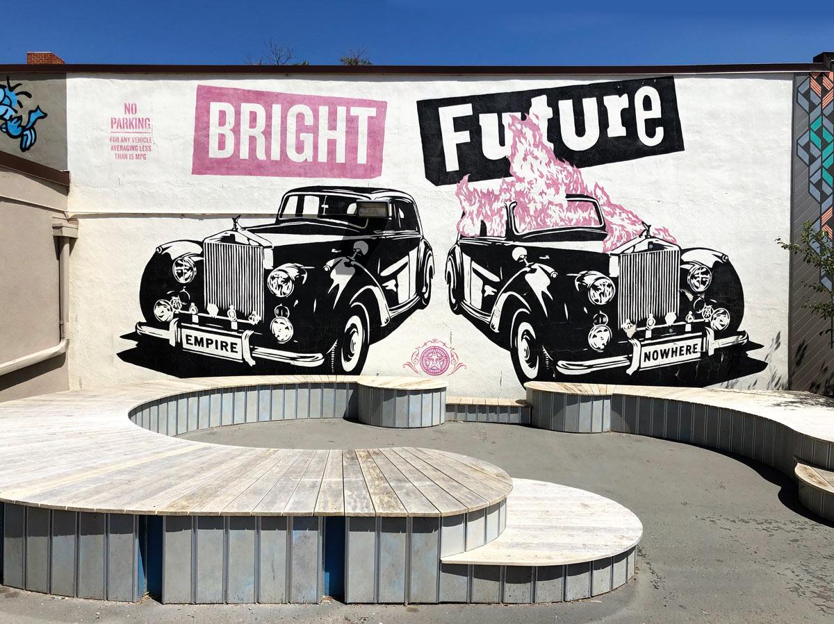 """bemalte Wand mit zwei schwarzen Oldtimer und dem Schriftzug """"Bright Future"""""""