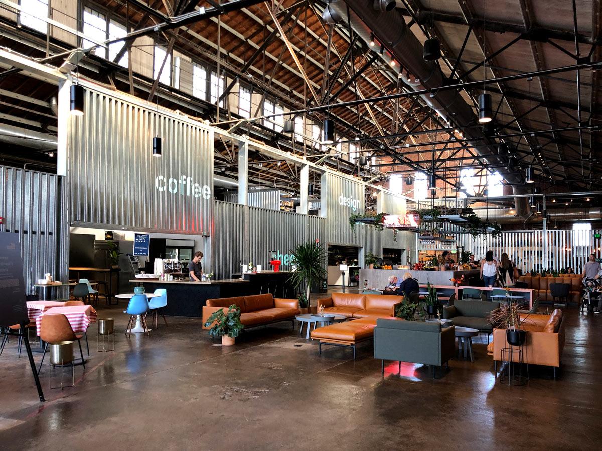 Hippe Lagerhalle umfunktioniert zu einer Markthalle mit Sitzgelegenheiten