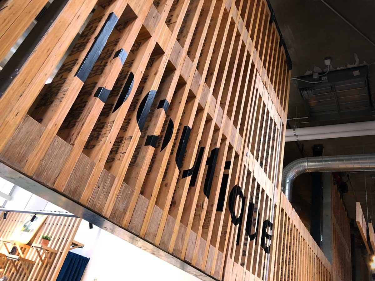 Bretterwand in Lagerhalle mit Schriftzug