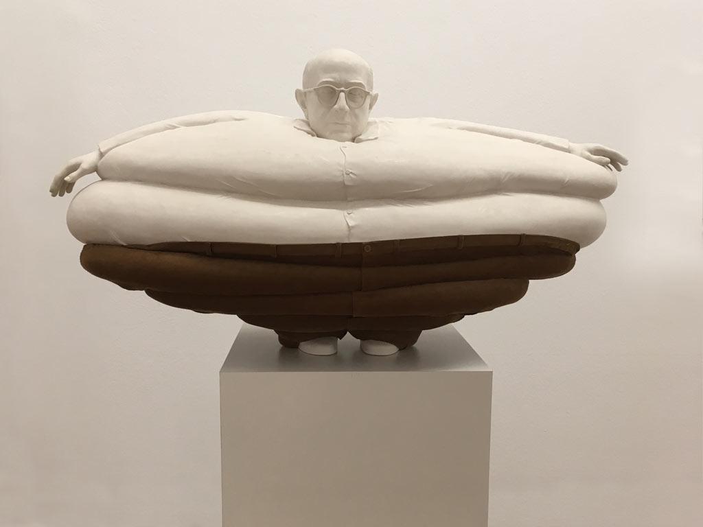 humorvolle Skulptur eines fetten, kleines Mannes, der auf seltsame Weise gestaucht wirkt