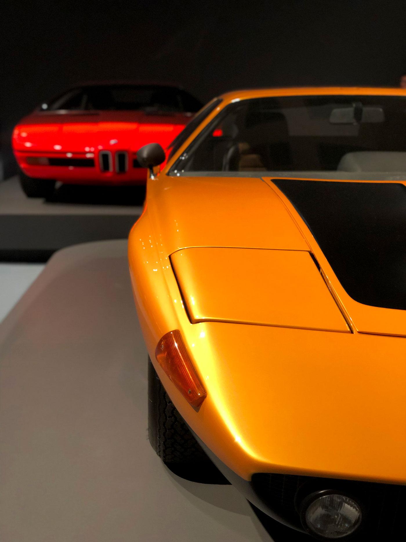 Im Vordergrund ein orangefarbener Sportwagen scharf, im Hintergrund ein roter Sportwagen unscharf