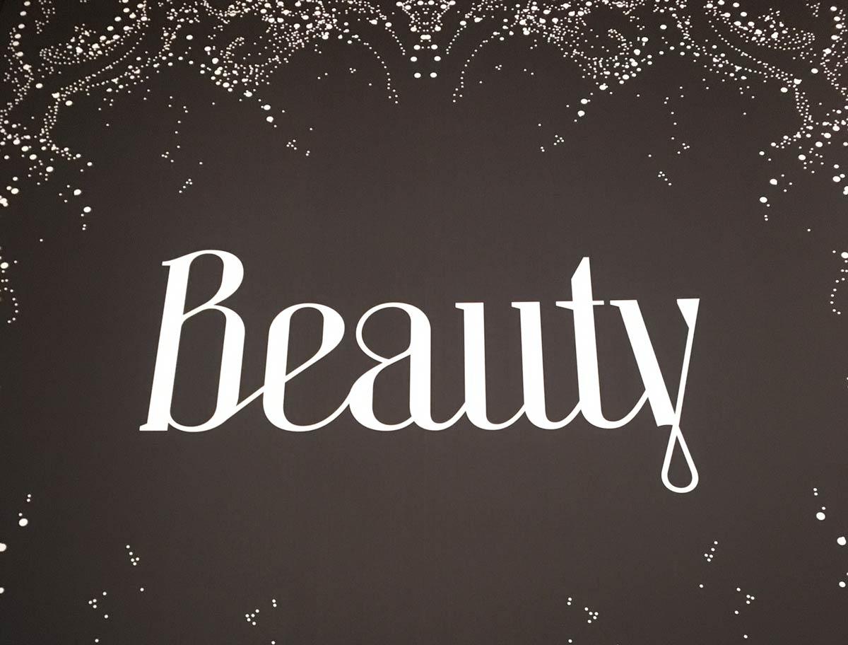 Beauty Schriftzug auf dunklem Untergrund mit dekorativen Elementen