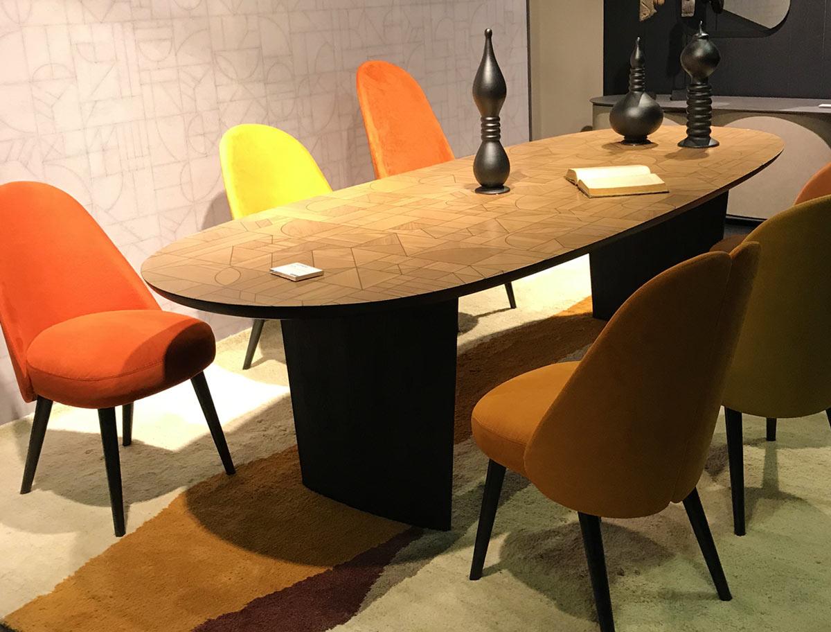 Esstisch aus Holz mit bunten, knalligen StühlenEsstisch aus Holz mit bunten, knalligen Stühlen