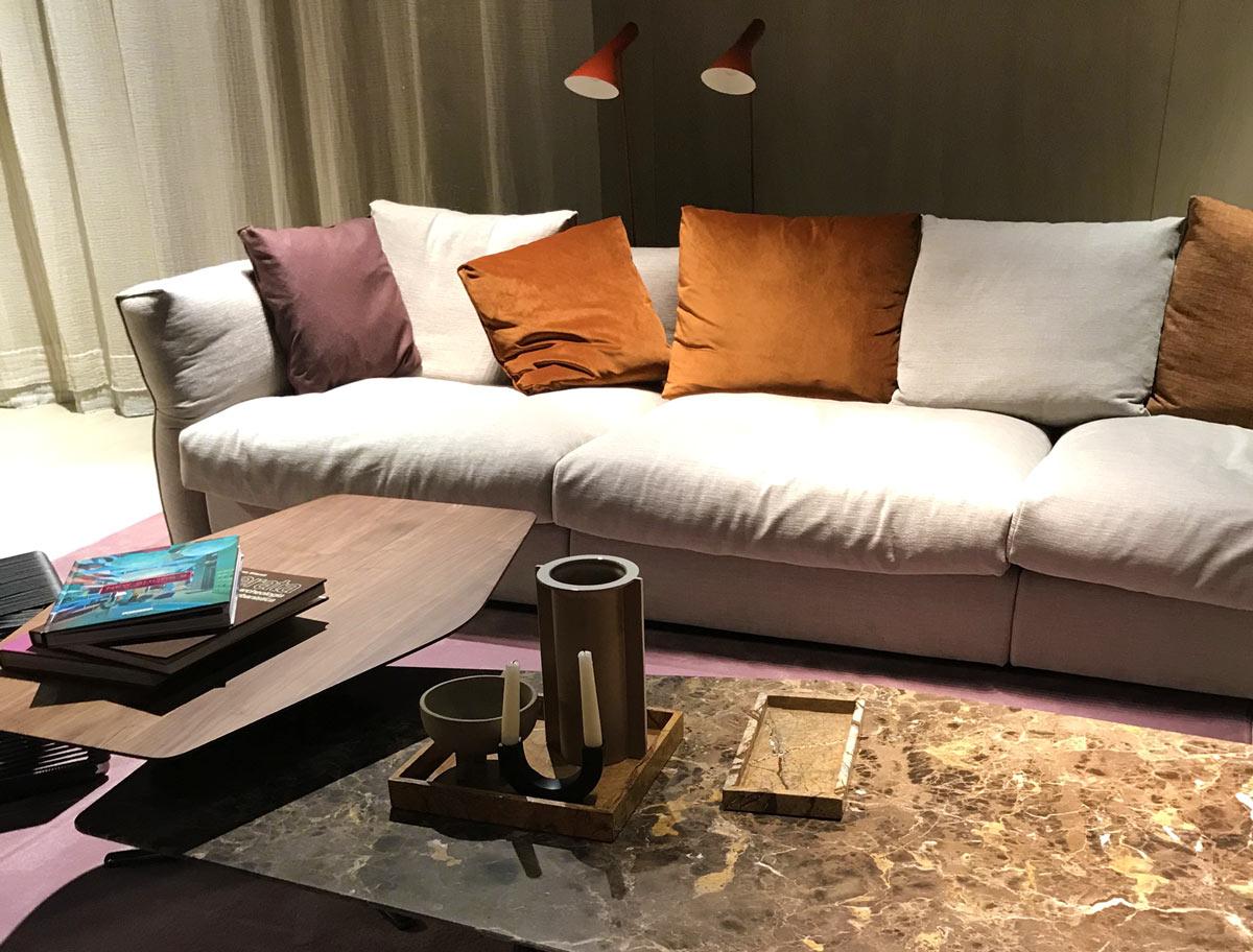 Wohnzimmerlandschaft mit Samt, kuscheligen Kissen und Holz- und Marmor-Tischen